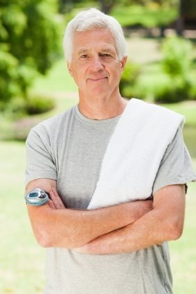 A man is in a sunny park ready to go jogging and is looking at the camera